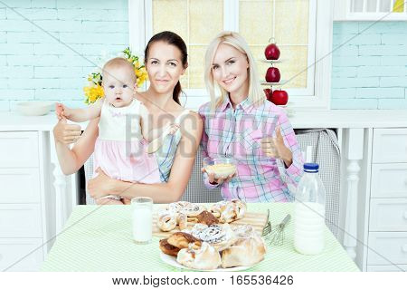 Pretty women in the kitchen with the baby they prepare food.