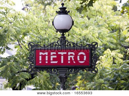 Traditional Paris metro sign with trees in the background