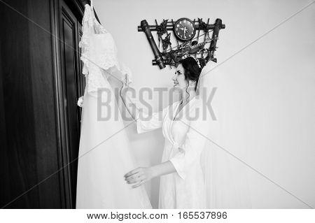Smiling Brunette Bride Wearing On White Silk Gown Robe Holding Her Wedding Dress On Hangers.
