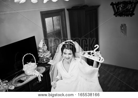 Smiling Brunette Bride Wearing On White Silk Gown Robe Holding Her Wedding Dress On Hangers. Black A