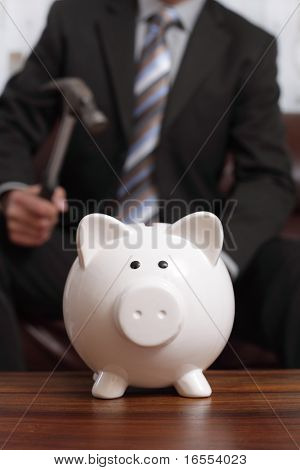 Businessman with hammer about to smash piggy bank to get at corporate savings