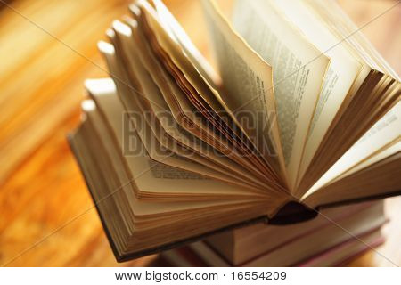 Book or bible on top of a stack of books on a wooden desk in library or classroom