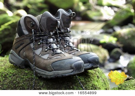 Walking boots in front of a mountain stream in a forest landscape