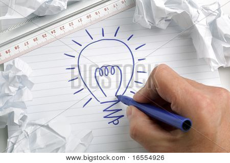 Businessmans hand drawing a light bulb, concept for brainstorming and inspiration