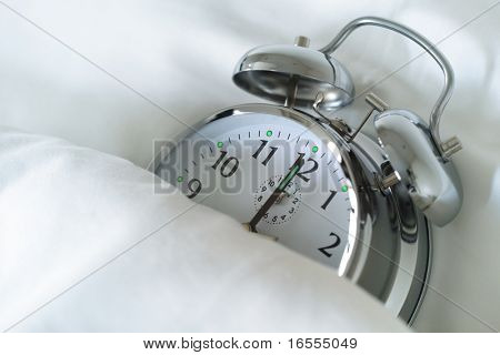Alarm clock in bed concept for overslept or bed time
