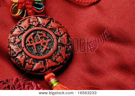 Traditional decorative accessories on Jin-Silk background.The characters on the face of accessories means