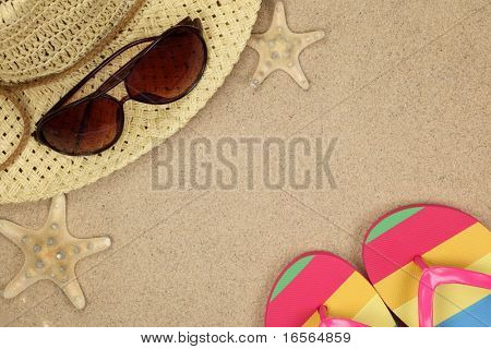 Colorful summer beachwear, flip flops, hat, sunglasses and starfish on sand beach.