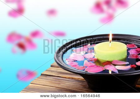 Spa  still life with candle and rose petals over bright background.