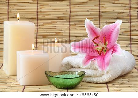 Spa still life with candles,bath-salt and towel on bamboo mat.