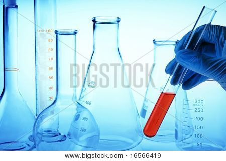 Scientist's hand holding test tube with red liquid in laboratory.
