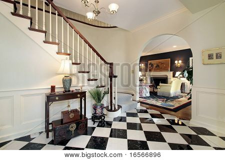 Checkerboard floor in foyer with stairway