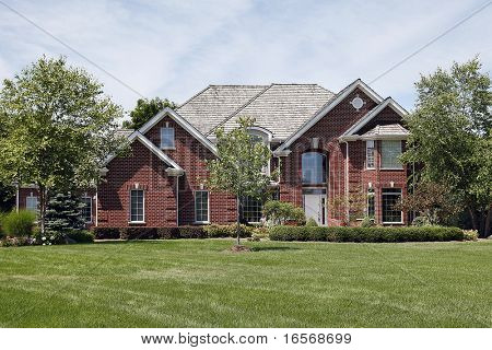Large brick home with large window above front door