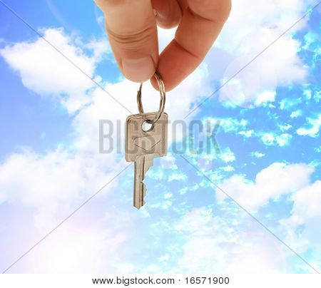 man hand holding key in front of a house