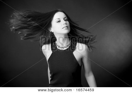 Portrait of a beautiful young woman with flying dark hair
