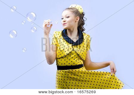beautiful young woman blowing soap bubbles on blue background