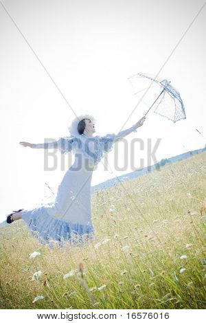 Beautiful woman in vintage dress walking across a field