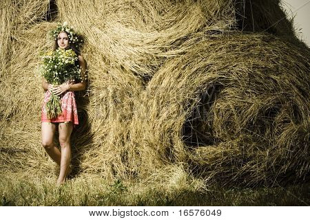 Beautiful woman with bouquet of flowers near a haystack