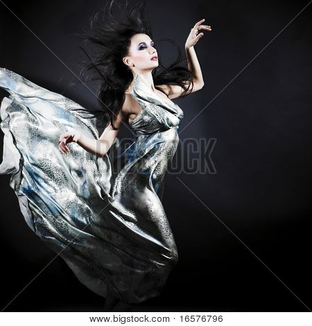 Portrait of a dancing sexy young woman with flying hair and silk dress