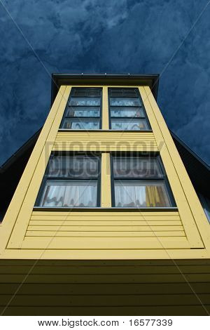 Detail of a yellow house against a blue sky