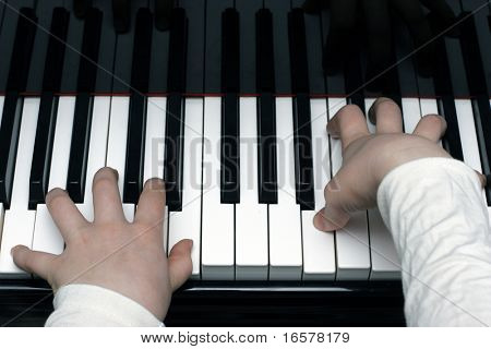 Kid playing the piano during piano lesson