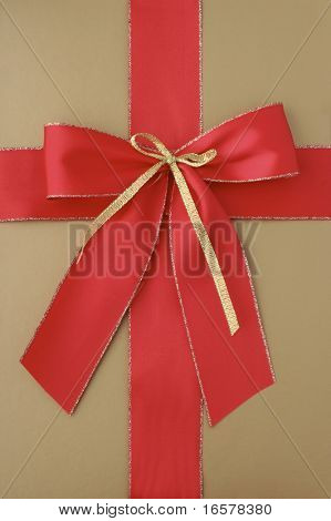 Close-up of a classic giftbox in gold and with a red ribbon