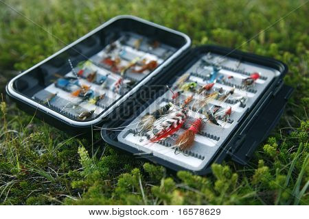 Flyfishing box full of colorful flies - short depth of field