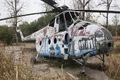 stock photo of rotor plane  - Wreck of an Old Soviet military chopper in a garden outdoor - JPG
