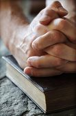 stock photo of praying hands  - Hands folded in prayer over a Holy Bible resting on a stone baptismal font - JPG