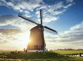 Windmill And Silhouette Of A Man At Sunrise In Netherlands poster
