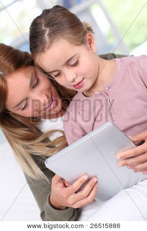 Mother and child using electronic tablet at home