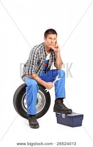 A thoughtfull mechanic sitting on a spare tire and holding a wrench isolated on white background