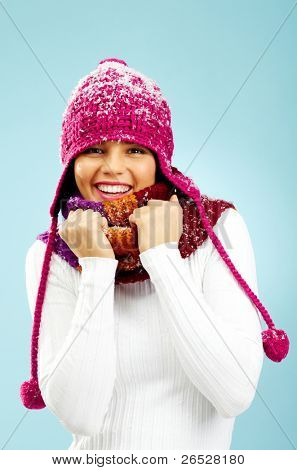 Portrait of pretty woman in knitted winter cap and scarf looking at camera with smile