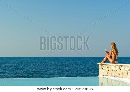 Woman In White Bikini Sitting Near Infinity Pool