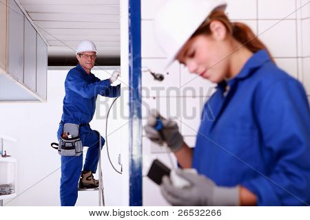 Mentor supervising female electrical engineer