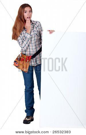 A handywoman amazed by a billboard.