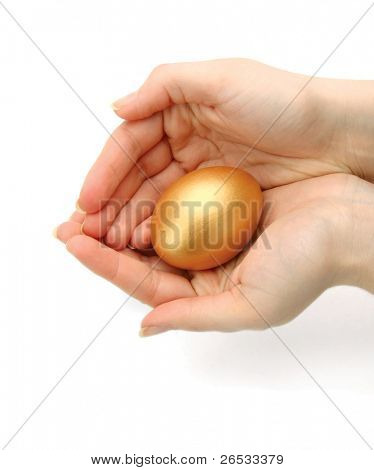 A golden egg in a female hand isolated on white background