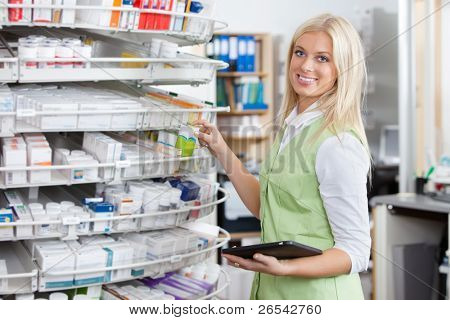 Portrait of female pharmacist holding tablet PC at pharmacy