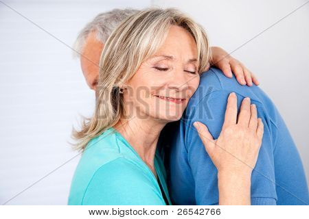 Wife embracing her husband with eyes closed