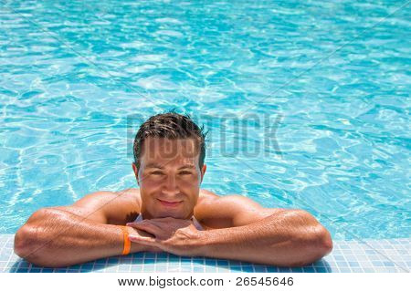 Young wet sexy muscular man posing in the swimming pool