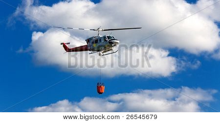 Fire fighting helicopter with waterbag on his way to combat the forest fire