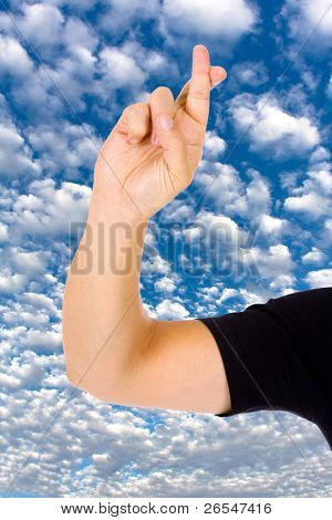Close up of a hand with fingers crossed over a blue sky with clouds