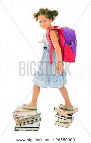 Portrait of litle girl with backpack walking from top to top of book piles