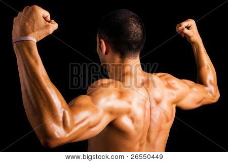 Portrait of a strong back of a young muscular man against dark background