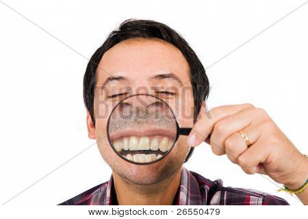 Image of a funny man with magnifying glass held up to face, enlarging mouth and teeth. Isolated