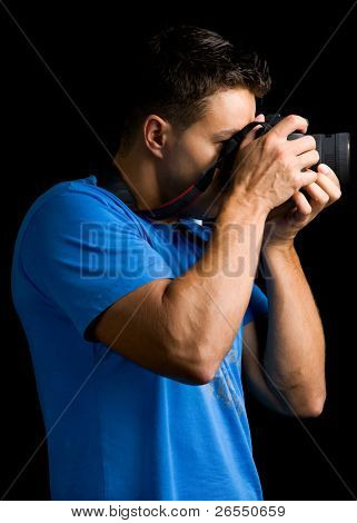 Photographer with camera against black background