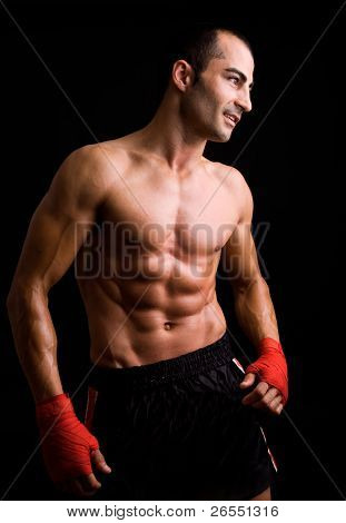 Young Boxer fighter posing against black background