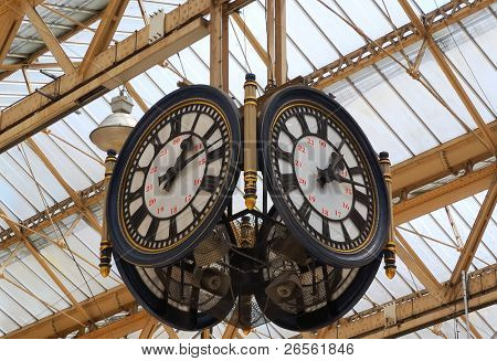 A train station clock with four faces and speakers