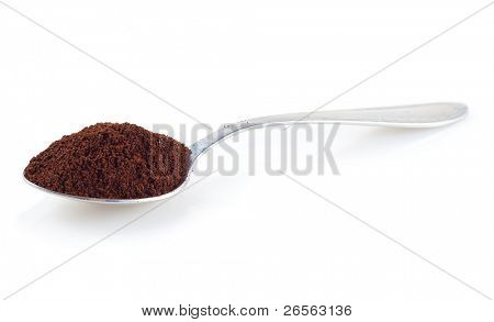 Shiny silver spoon filled with coffee on a white background