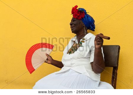 HAVANA-NOVEMBER 30:Old lady with a fine cigar dressed in typical cuban clothes November 30, 2010 in Havana.