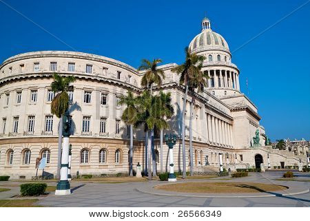 Landscape view of the Capitol building ( El Capitolio )  in Havana with a beautiful blue sky and royal palm trees